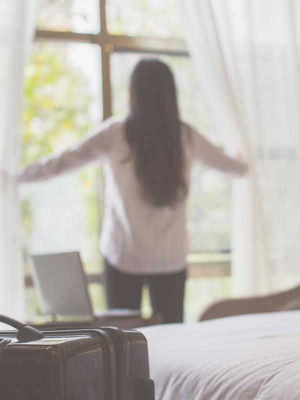 businesswoman open window in hotel room maleta derby hotels collection