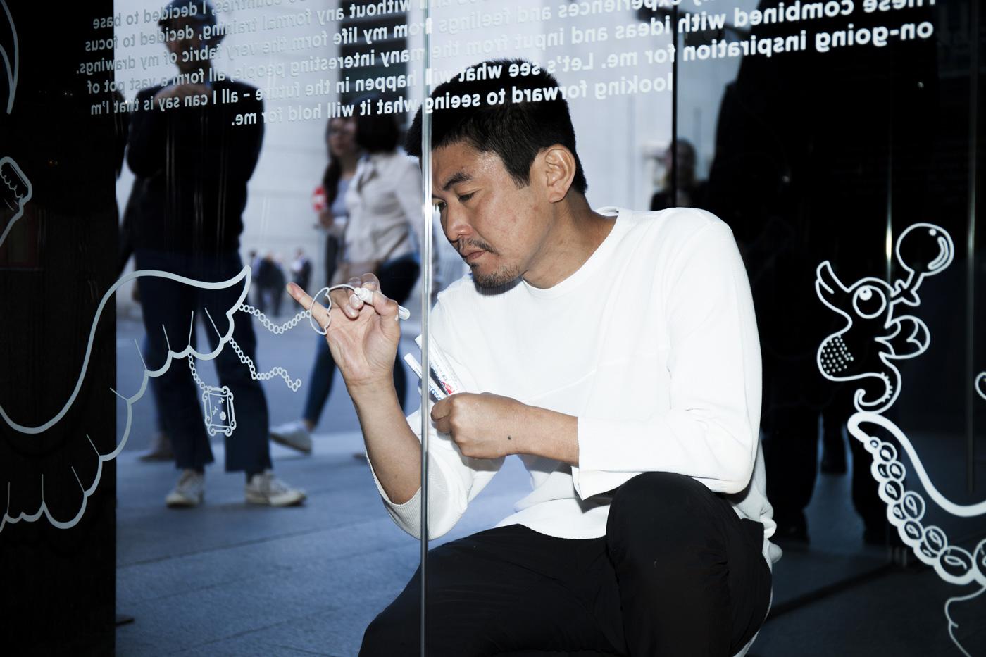 Yoshi Sislay dibujando en la cristalera del Hotel Urban